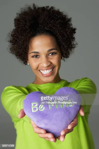 young woman holding heart - valentines african american stock pictures, royalty-free photos & images