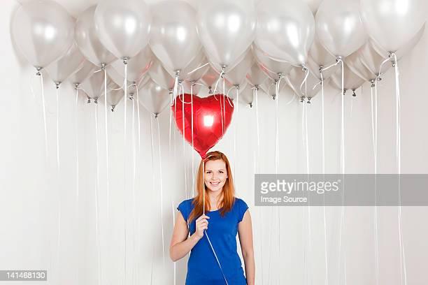 Junge Frau hält herzförmigen Ballons