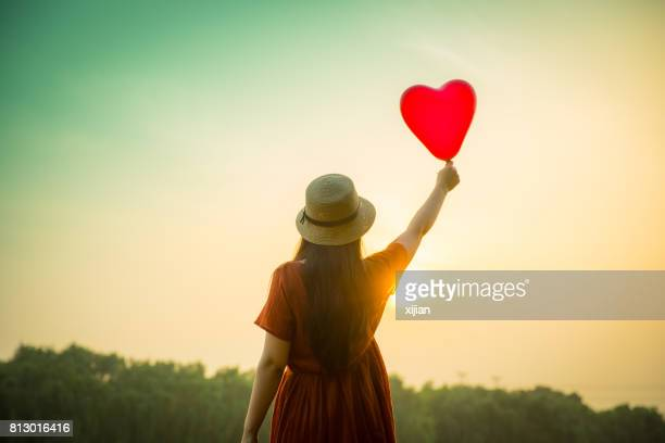 Young woman holding heart-shaped balloon