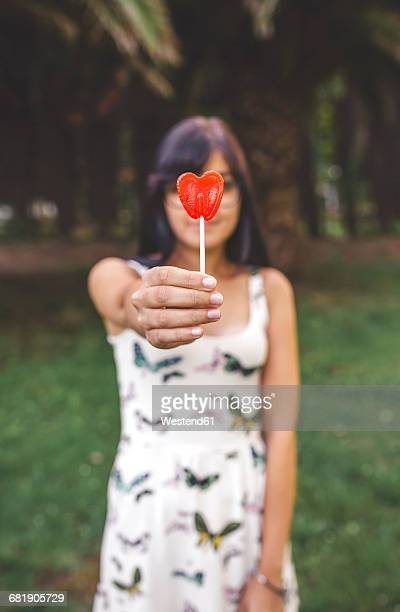 Young woman holding heart-shaped lollipop