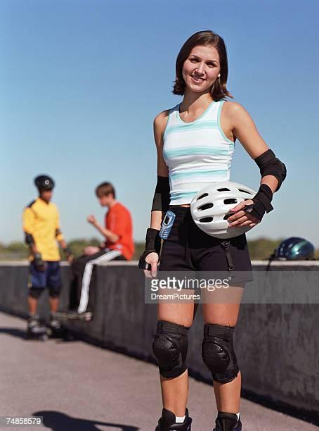 young woman holding helmet, young men on background, smiling - caneleira roupa desportiva de proteção imagens e fotografias de stock