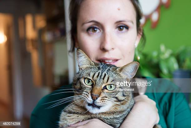 Young woman holding her cat at home