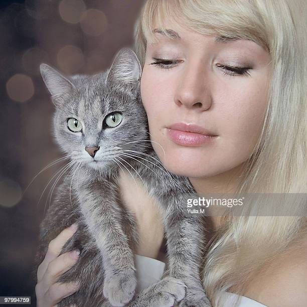 A young woman holding her cat