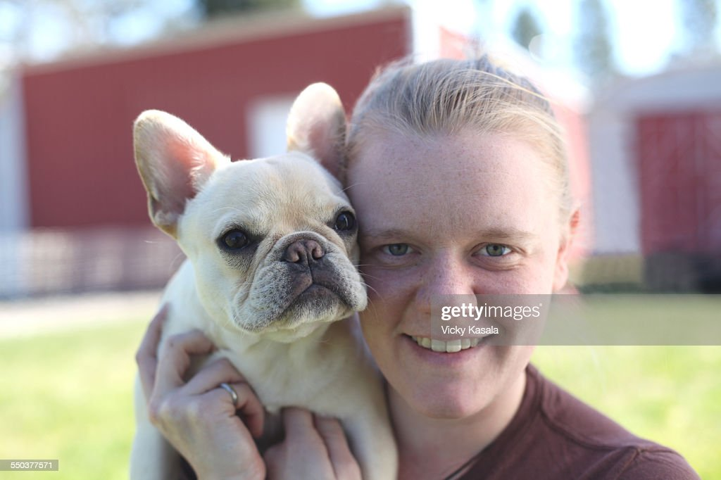 Young woman holding her French bulldog puppy. : Stock Photo
