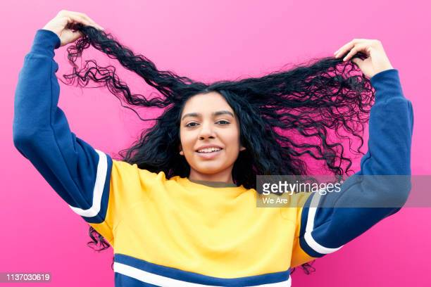 young woman holding her hair and laughing - long hair stock pictures, royalty-free photos & images