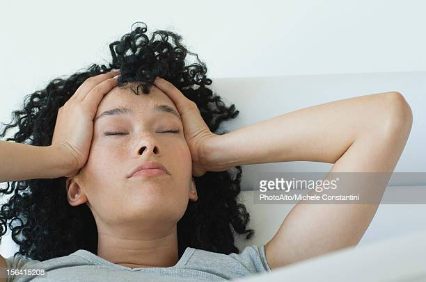 young woman holding her head, eyes closed - hangover stock photos and pictures
