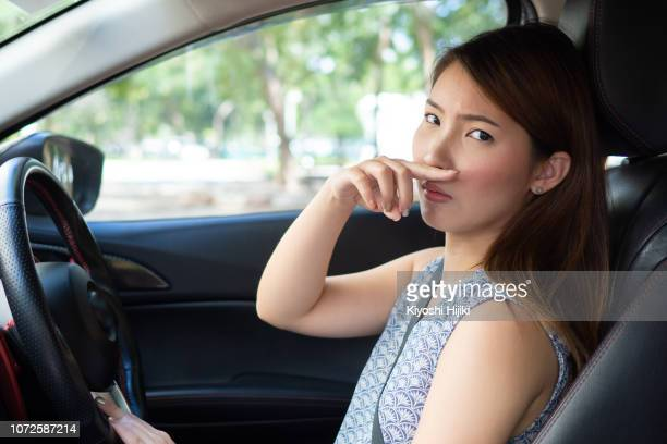 young woman holding her nose because of bad smell in car - olor desagradable fotografías e imágenes de stock
