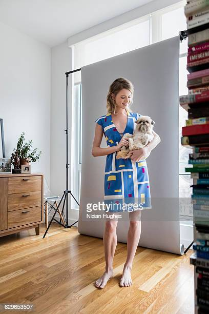 young woman holding her pet dog in apartment