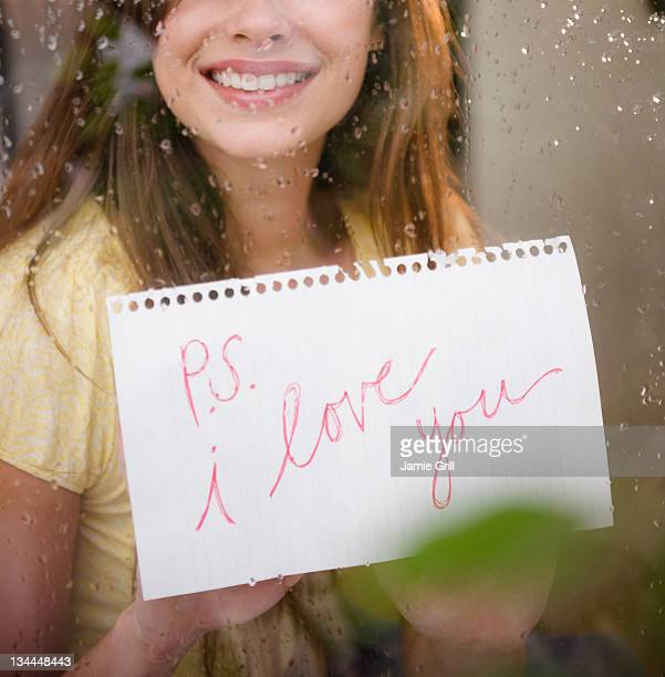 "young woman holding ""i love you"" sign at window - i love you photos et images de collection"