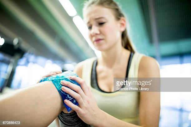 Young woman holding ice pack on knee