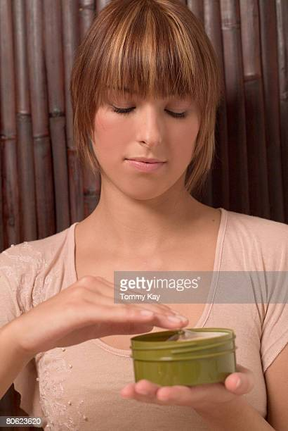 Young Woman Holding Jar with Cream