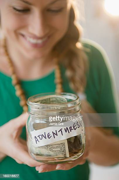 Young woman holding jar with money