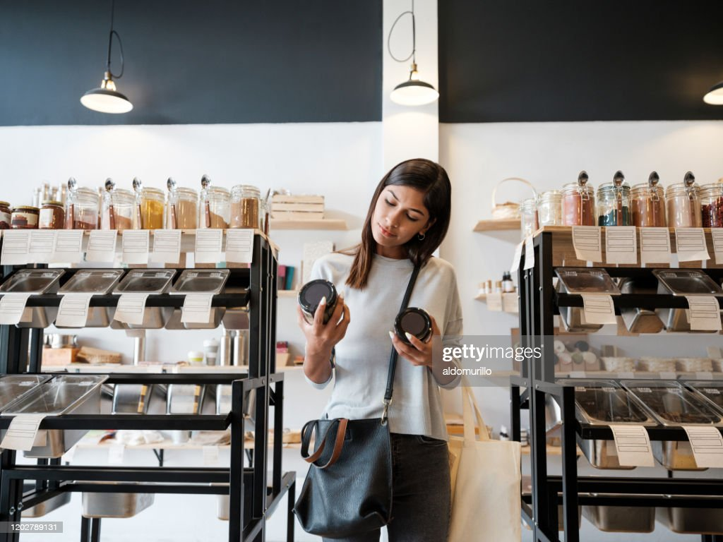Young woman holding jars in zero waste store : Stock Photo