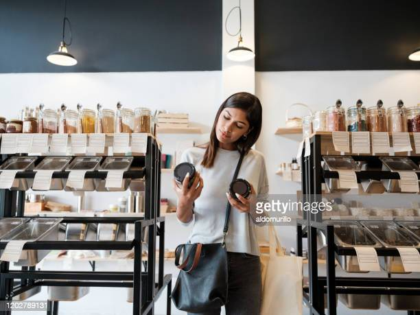 young woman holding jars in zero waste store - consumerism stock pictures, royalty-free photos & images