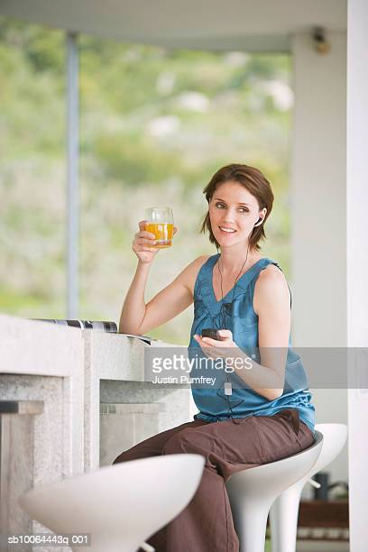 young woman holding juice glass, listening mp3 player - mp3 juices stock photos and pictures