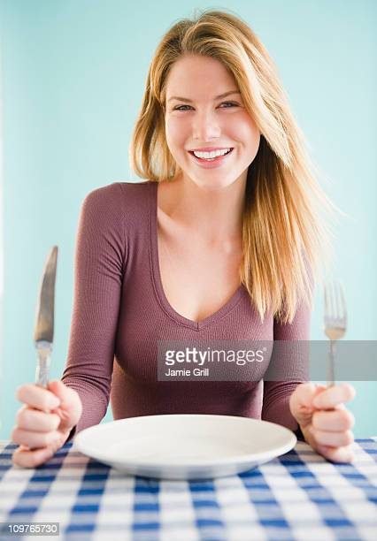 Young woman holding knife and fork