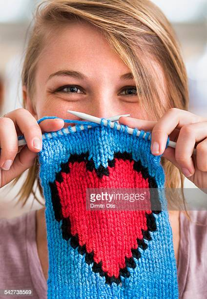 Young woman holding knitted red heart scarf