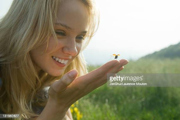 Young woman holding ladybug as it takes off in flight