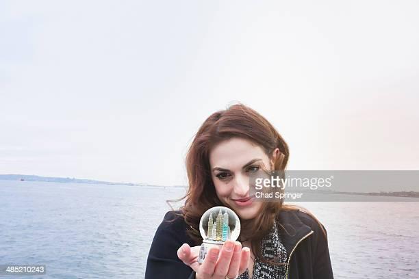 Young woman holding landmark snow globe, New York, USA