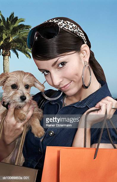 Young woman holding lap dog and shopping bags outdoors, portrait