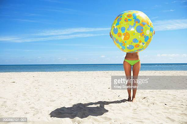Young woman holding large beach ball on beach