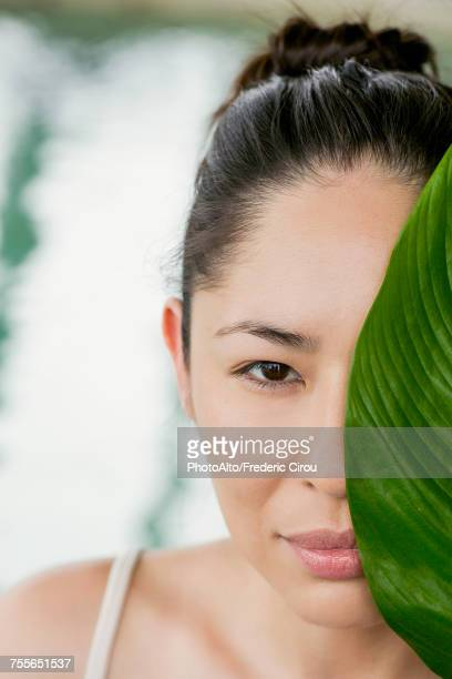 Young woman holding large leaf in front of her face and smiling