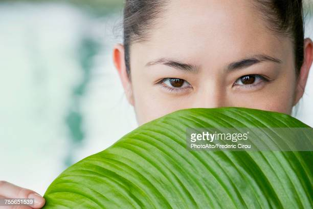 Young woman holding large leaf in front of her face