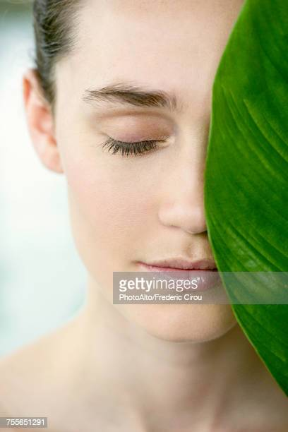 Young woman holding large leaf over half of her face, portrait