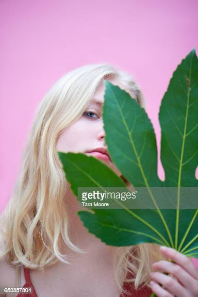 young woman holding large leaf