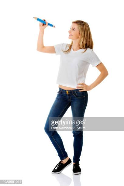 young woman holding large pencil against white background - one young woman only stock pictures, royalty-free photos & images