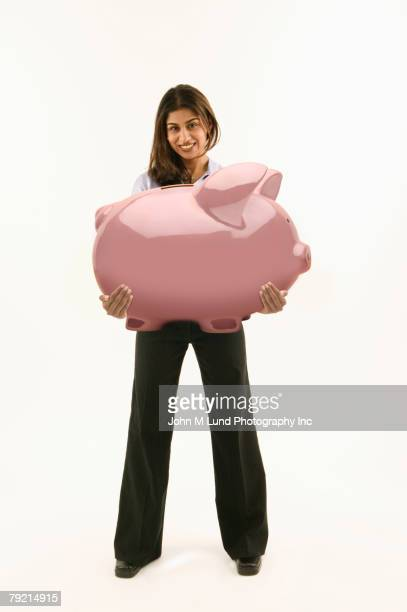 Young woman holding large piggy bank