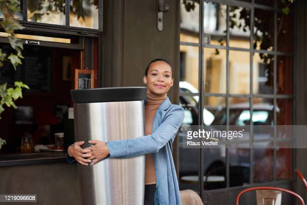 young woman holding large reusable coffee cup outside cafe - carrying stock pictures, royalty-free photos & images