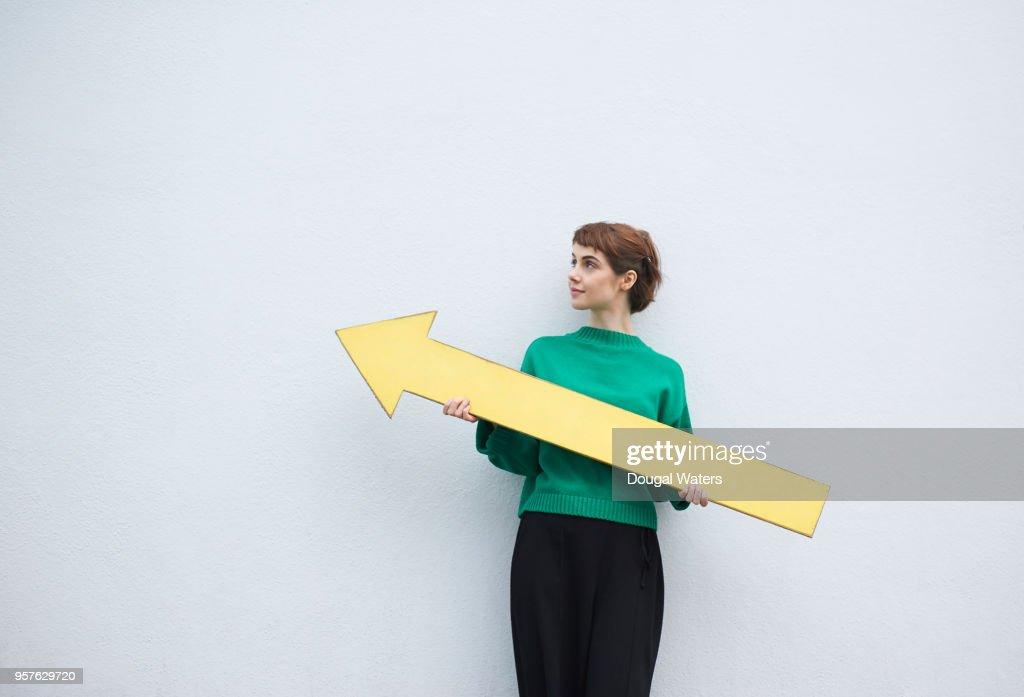 Young woman holding large yellow arrow sign. : Stock Photo
