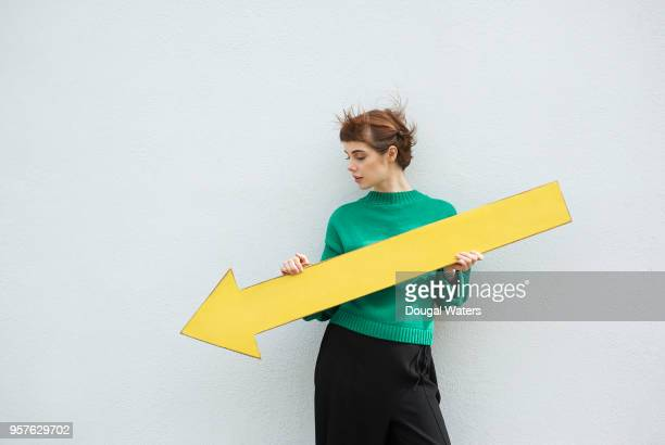 young woman holding large yellow arrow sign pointing down. - decline stock pictures, royalty-free photos & images