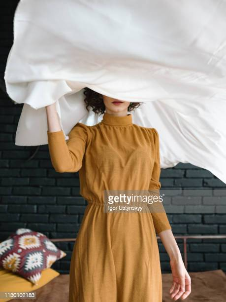 young woman holding laundry - sheet bedding stock pictures, royalty-free photos & images