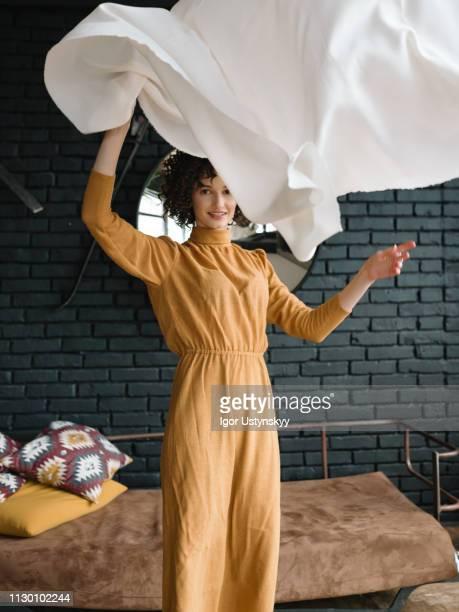 young woman holding laundry - sauber stock-fotos und bilder