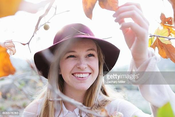 Young woman holding leaf, smiling, outdoors