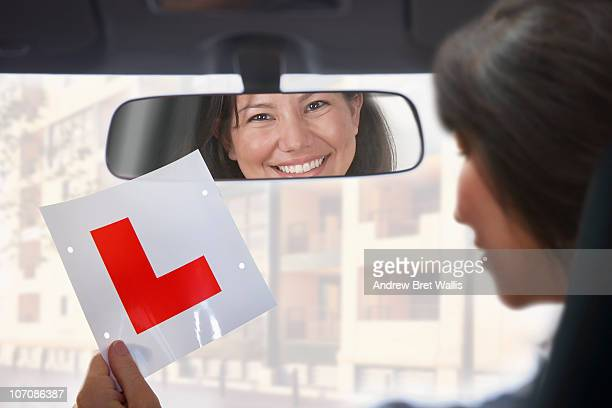 Young woman holding learner driver plate in car