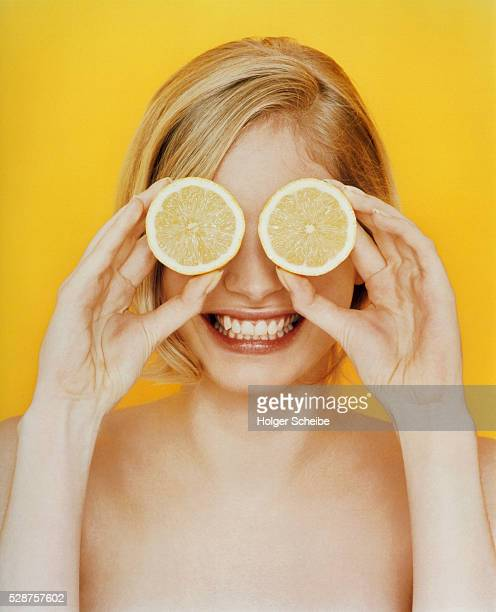 Young woman holding lemons in front of her eyes