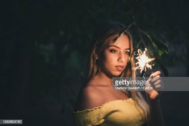 young woman holding lit sparkler at night - off shoulder stock pictures, royalty-free photos & images