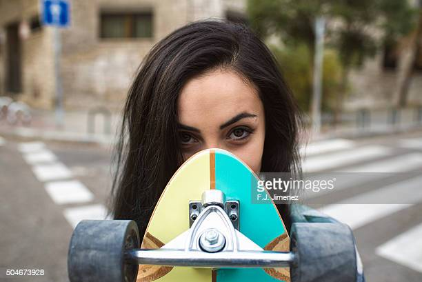 Young woman holding longboard