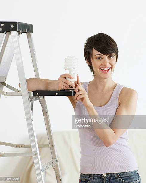 Young Woman Holding Long-Life Light bulb