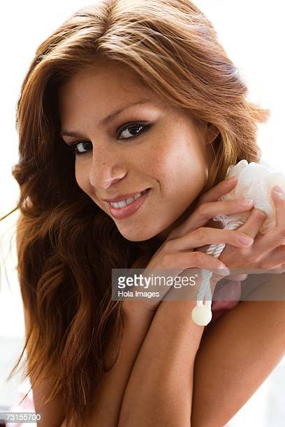 young woman holding loofah sponge - loofah stock photos and pictures