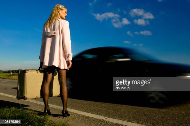 young woman holding luggage and standing on side of road - seamed stockings stock photos and pictures