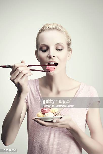 Young woman holding macaroon with chopsticks, portrait
