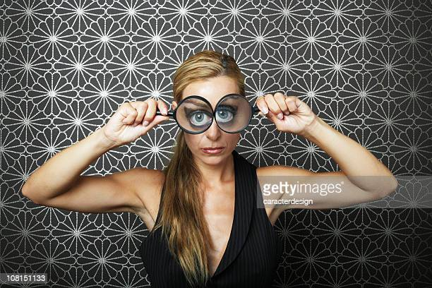 Young Woman Holding Magnifying Glasses To Both Eyes