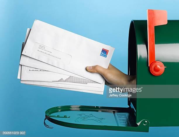 young woman holding mail out of mailbox, side view - responder - fotografias e filmes do acervo