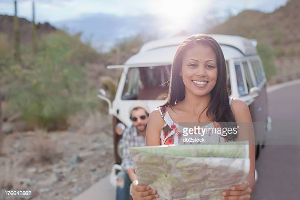 Young woman holding map on road trip, smiling