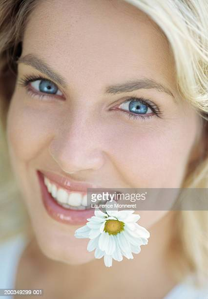 Young woman holding marguerite flower in teeth, close-up