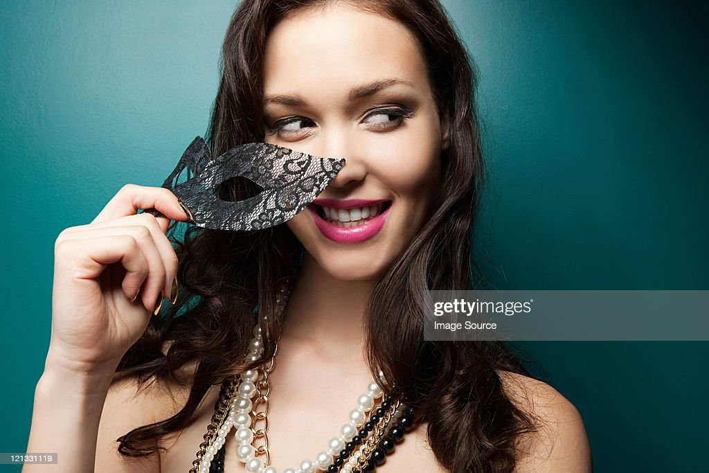 Young woman holding masquerade mask, portrait : Stock Photo